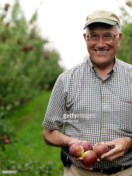 Apple farmer holding applies in orchard, portrait