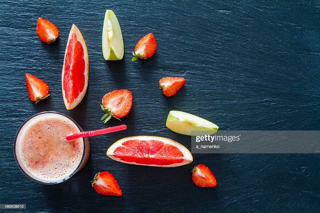 Apple, grapefruit and strawberry smoothie and ingredients, dark stone background : Bildbanksbilder