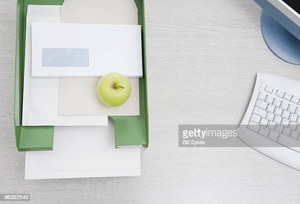 apple in in-tray on desk