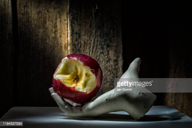 apple in mannequin hand - ian gwinn stock pictures, royalty-free photos & images