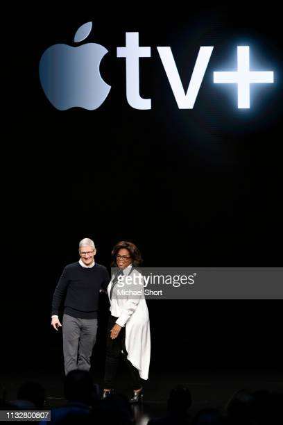 Apple Inc CEO Tim Cook and Oprah Winfrey stand onstage during a company product launch event at the Steve Jobs Theater at Apple Park on March 25 2019...