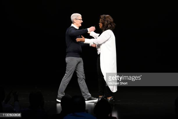 Apple Inc CEO Tim Cook hugs Oprah Winfrey during a company product launch event at the Steve Jobs Theater at Apple Park on March 25 2019 in Cupertino...