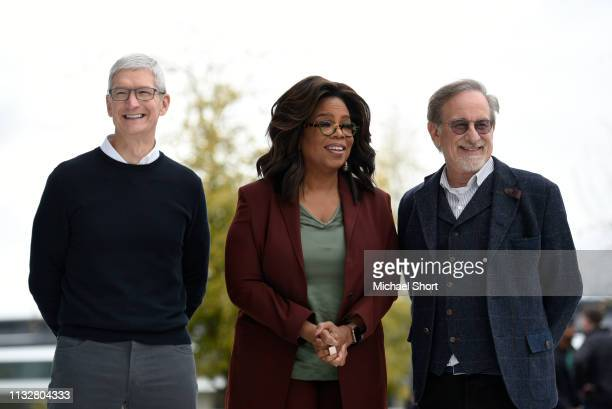 Apple Inc CEO Tim Cook Oprah Winfrey and filmmaker Steven Spielberg pose for photos during an Apple product launch event at the Steve Jobs Theater at...