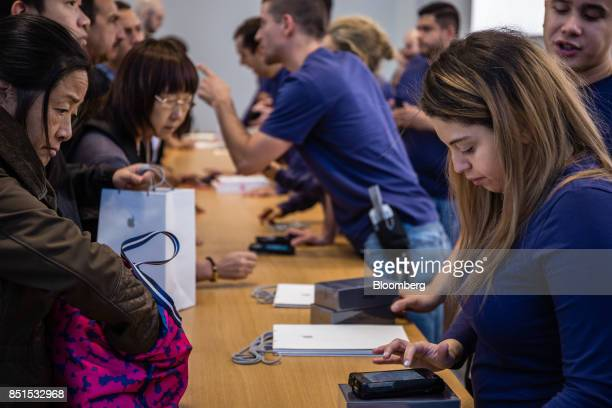 Apple Inc employees assist customers with purchases during the sales launch of the iPhone 8 smartphone Apple watch series 3 device and Apple TV 4K...