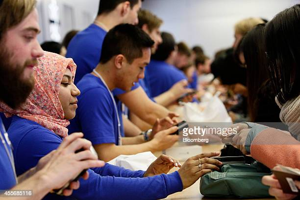 Apple Inc. Employees assist customers with their purchases during the sales launch of the iPhone 6 and iPhone 6 Plus at the company's George Street...