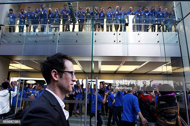 Apple Inc employees cheer as doors open at the company's George Street store for the sales launch of the iPhone 6 and iPhone 6 Plus in Sydney...
