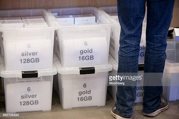Apple Inc. IPhone smartphones sit in color-coded crates behind a sales counter during the sales launch of the iPhone 6 and iPhone 6 Plus at the Apple...
