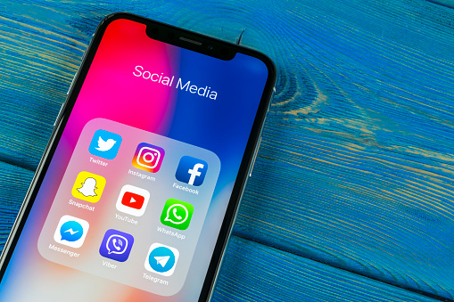 Apple iPhone X on office desk with icons of social media facebook, instagram, twitter, snapchat application on screen. Social network. Starting social media app. 962440944
