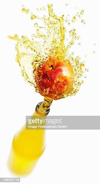 Apple juice splashing out of bottle on apple