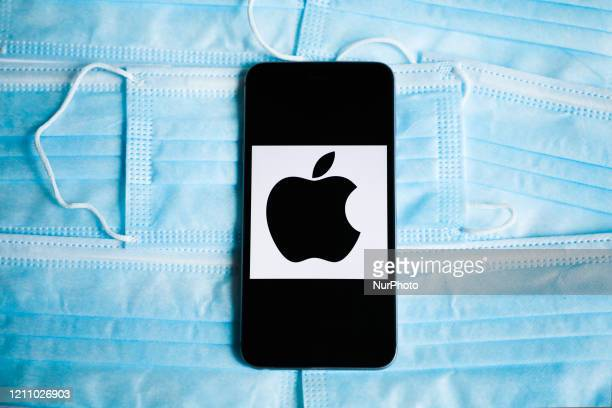 Apple logo is displayed on a mobile phone screen photographed on surgical masks background for illustration photo during the spread of coronavirus....