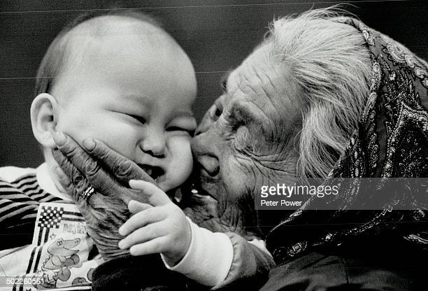 Apple of her eye: Jeannie Minaweetaituk; a 72-year-old Inuit great-grandmother; kisses her 1-year-old grandson; Harry Kudiu; in Kuujjuarapik; Que.