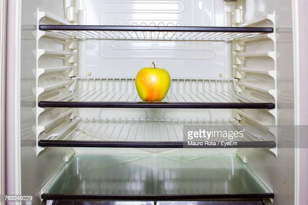 apple on shelf in refrigerator - domestic kitchen stock pictures, royalty-free photos & images
