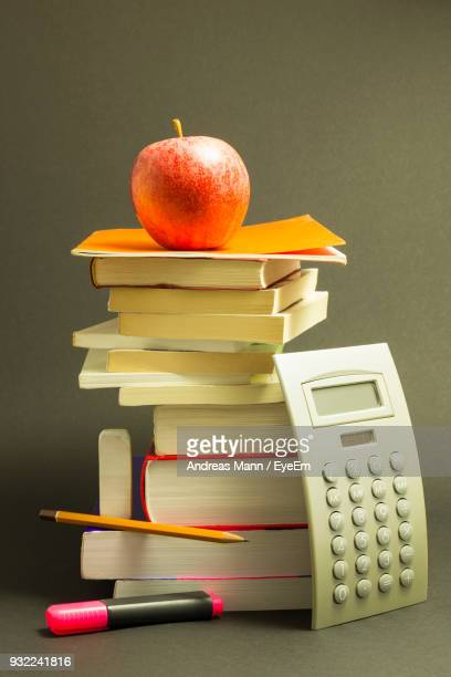 Apple On Stack Of Books Against Gray Background
