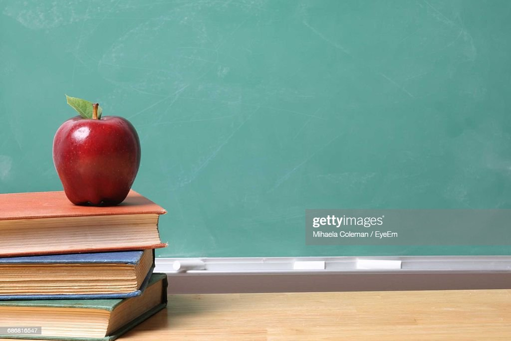 Apple On Stacked Books At Table By Green Board : Stock Photo