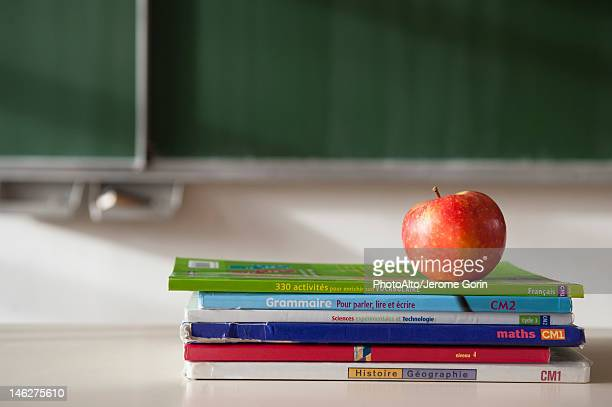 apple on top of stacked books - textbook stock pictures, royalty-free photos & images