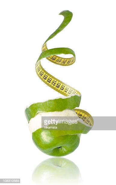 apple peeled with twisting skin as measuring tape - centimetre stock photos and pictures