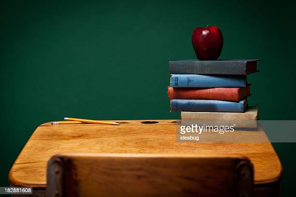 Apple, Pencils and Old Books on School Desk by Chalkboard