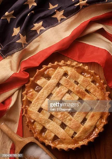 Apple pie next to US flag, overhead view