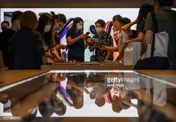 Apple staff and customers are seen at the official opening of the new Apple Store in the Sanlitun shopping area on July 17 2020 in Beijing China The...