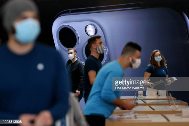 Apple staff members assist customers at the Bondi Junction Apple Store on May 07, 2020 in Sydney, Australia. Apple stores across Australia reopened...