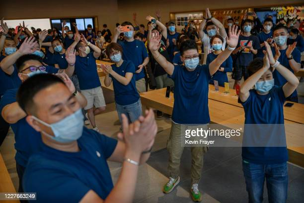 Apple staff welcome customers as they enter in small groups at the official opening of the new Apple Store in the Sanlitun shopping area on July 17...