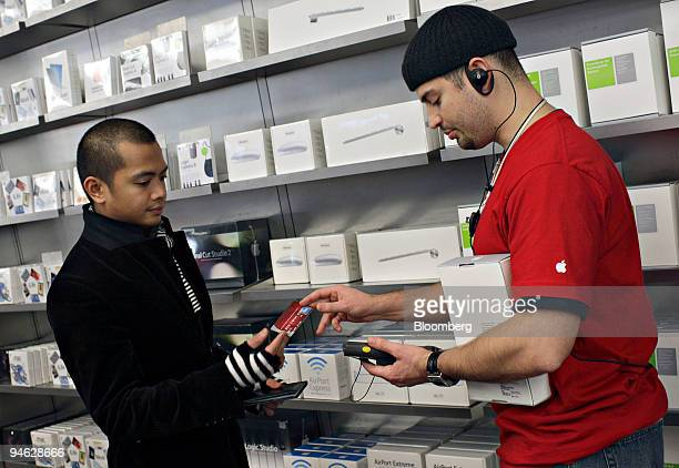 Apple Store employee Alex Alvarez right takes the credit card of customer Nic Aldana as he checksout using a handheld device in the Apple Store on...