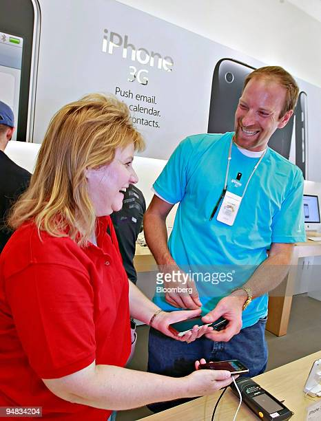 Apple Store employee Kevin Winsness right laughs with customer Sharon Walton as he helps activate her new iPhone 3G inside an Apple store in Salt...