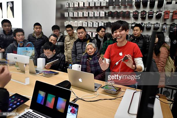 Apple Store employees display products and answer questions during the grand opening of an Apple Store in Jiefangbei Yuzhong District on January 31...