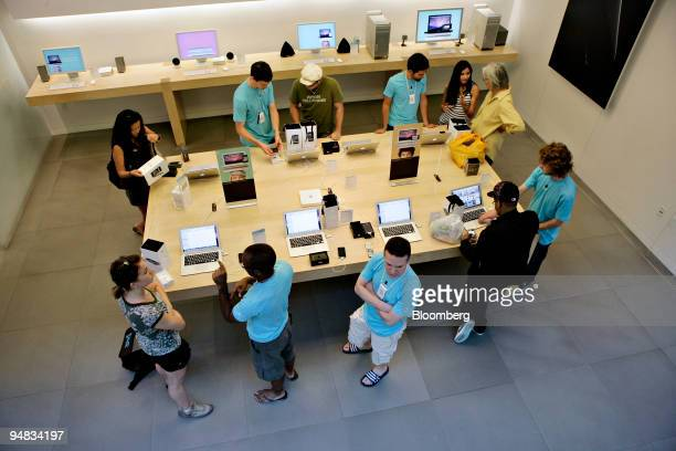 Apple Store employees in blue shirts assist customers with the activation of their iPhone 3G handsets in the Apple store in the SoHo neighborhood of...