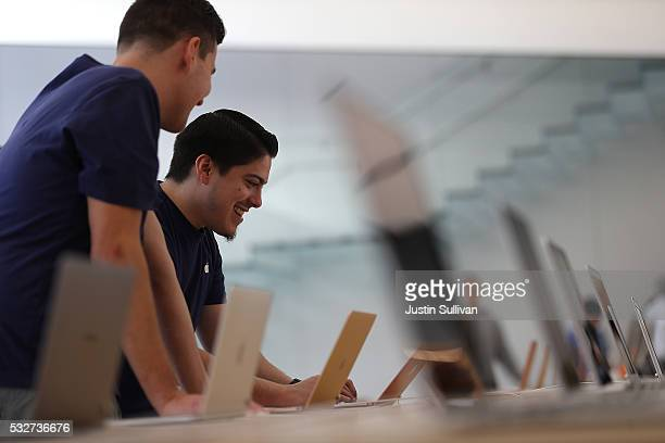 Apple Store employees look at a display of MacBook laptops during a press preview of the new flagship Apple Store on May 19 2016 in San Francisco...