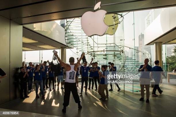 Apple store staff congratulate the first buyer of an iPhone 6 during its launch at an Apple store in Hong Kong on September 19 2014 The iPhone 6 has...
