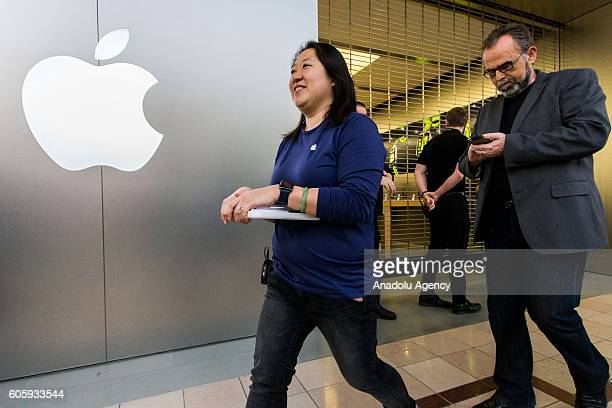 Apple store staffs guide the customers before the doors open as large crowds queue in line awaiting the release of iPhone's new models in front of...
