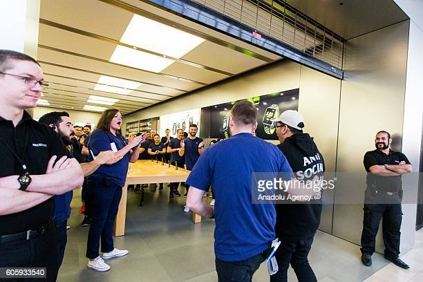 Apple store staffs guide the first customer as the doors opened while large crowds awaiting in the queue for the release of iPhone's new models in...
