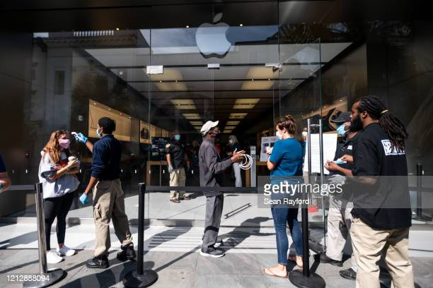 Apple Store workers and security guards prepare customers to enter the reopened store on May 13 2020 in Charleston South Carolina Customers had...