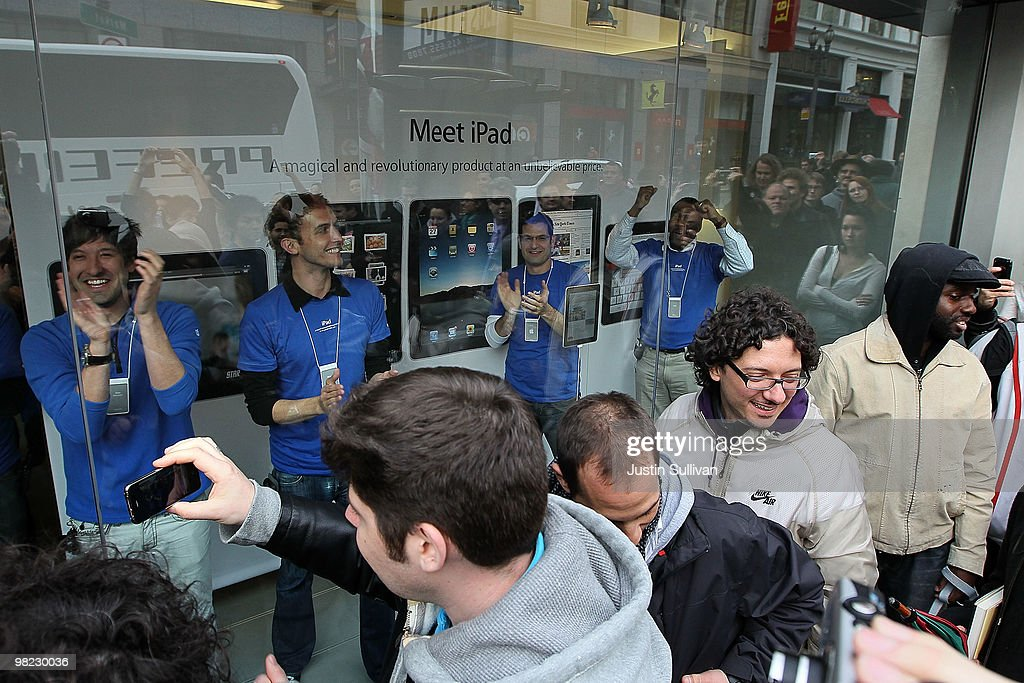 Apple store workers cheer in a display window before opening the store to customers to purchase the new iPad April 3, 2010 in San Francisco, California. Hundreds of people lined up hours before the Apple store opened to purchase the new iPad which debuted today.