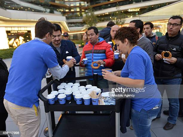 Apple Store workers serve tea to customers who waiting outside Zorlu Center as iPhone 6 and iPhone 6 Plus retail sales begin at Apple Store in Zorlu...