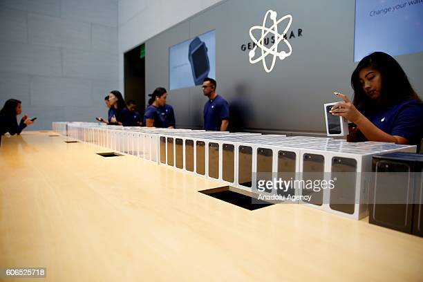 Apple store's personnels are seen after they opened the store for customers who wait to buy new iPhone 7 and 7 plus models in front of the Apple...