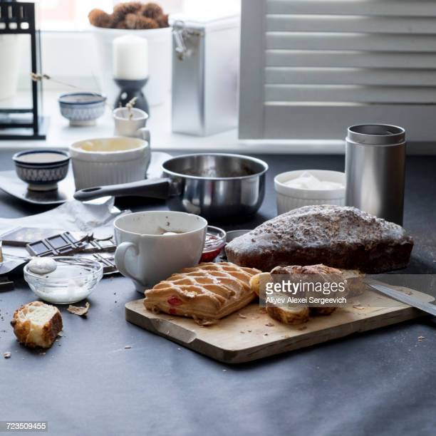 Apple strudel, chocolate, cake and ingredients on kitchen table