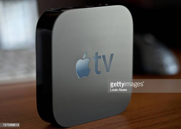 Apple TV standing vertically on a desk, clearly showing the Apple logo. Out of focus keyboard and mouse in the background.
