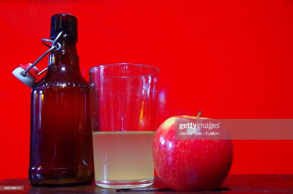 Apple With Juice In Drinking Glass And Bottle Against Red Wall : Foto stock