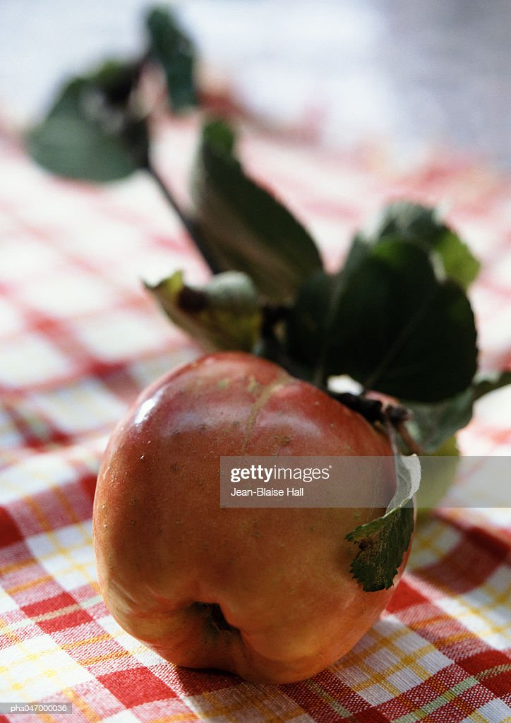 Apple with leaves on checkered tablecloth, close-up : Stockfoto