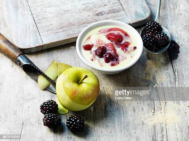 Apple with skin peeled, blackberries, apple and blackberry custard, white washed and scratched wooden surface