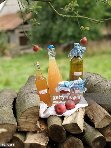 Apples and juice on log pile