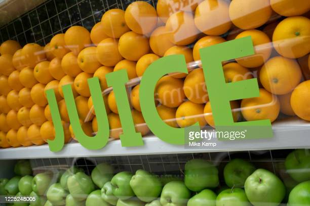 Apples and oranges in the window of a juice bar on 2nd June 2020 in Birmingham, United Kingdom. A juice bar is an establishment that primarily serves...