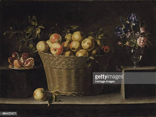 Apples in a wicker basket an pomegranate on a silver plate and flowers in a glass vase From a private collection