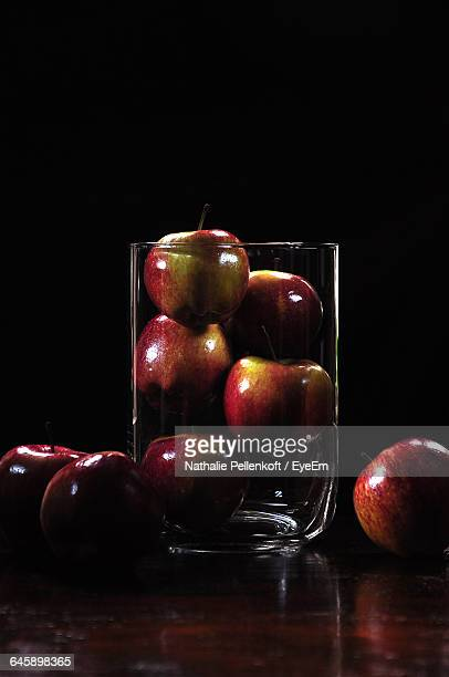 apples in glass on table against black background - nathalie pellenkoft stock pictures, royalty-free photos & images