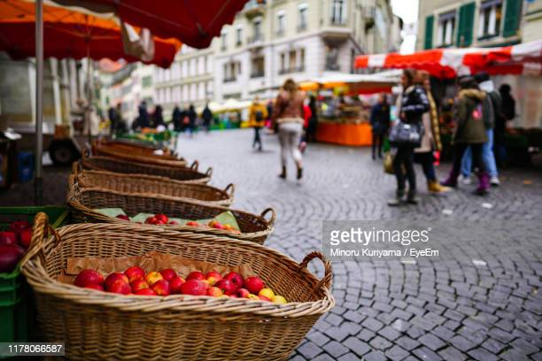 apples in wicker baskets for sale by people at street market - lausanne stock pictures, royalty-free photos & images