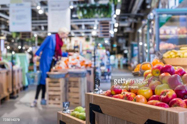 Apples in wooden crates with woman shopping at supermarket