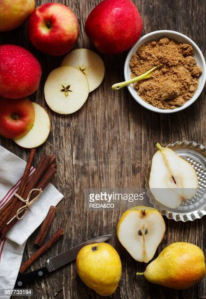 Apples pears cinnamon sticks and brown sugar on wooden background with copy space