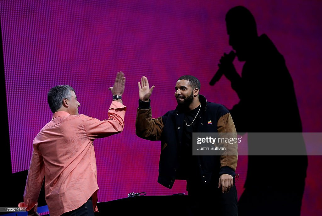 Apple's senior vice president of Internet Software and Services Eddy Cue (L) high fives with recording artist Drake during the Apple Music introduction at the Apple WWDC on June 8, 2015 in San Francisco, California. Apple's annual developers conference runs through June 12.